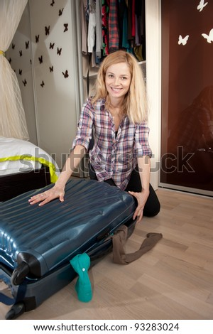 Young blonde girl packing her travel bag - stock photo