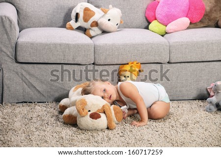 young blonde girl playing with soft toys on the carpet in the living room - stock photo