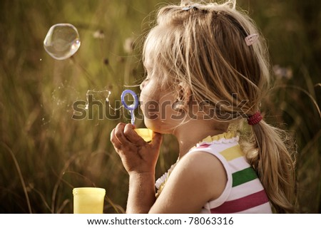 Young blonde girl plays in a field, blowing many bubbles - image is graded in a nostalgic tone