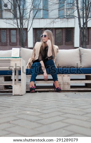 Young blonde girl posing in the street