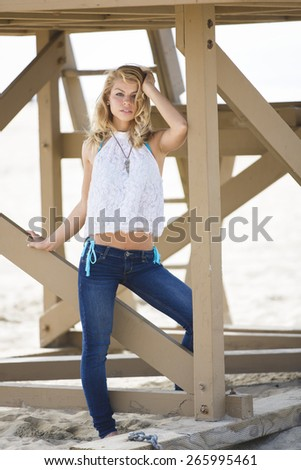 Young blonde girl posing outdoors under a bridge