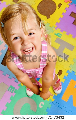 young blonde girl smiles as she learns the alphabet at playschool - stock photo
