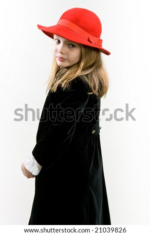 Young blonde girl standing turned right head turned back with red hat