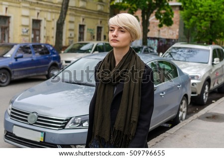 Young blonde girl walking on the city streets
