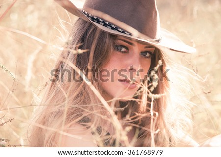 young blonde girl with cowboy hat outdoor in grass, summer day, closeup - stock photo