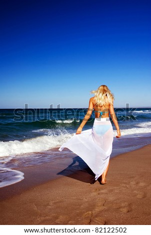 Young blonde girl with pareo on the sunny tropical beach - stock photo