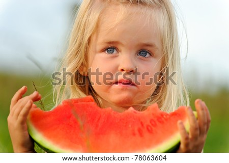 Young blonde girl wonders if she wants to continue eating this not so sweet watermelon - stock photo