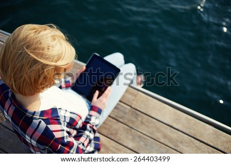 Young blonde hair woman sitting on a jetty next to a sea while using busy digital tablet with a blank screen, tourist woman searching information on tablet while relaxing on a pier after walk - stock photo