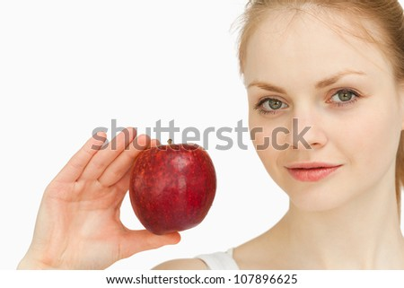 Young blonde-haired woman presenting an apple against white background