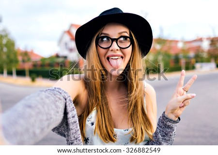 Young blonde hipster woman, making selfie, showing tongue, funny face, posing at countryside at autumn day, stylish hat and clear sunglasses. - stock photo