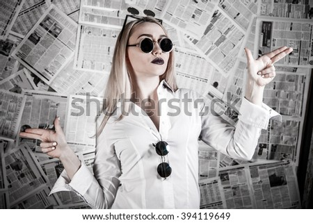 Young blonde in a sunglasses surrounded with newspapers - stock photo