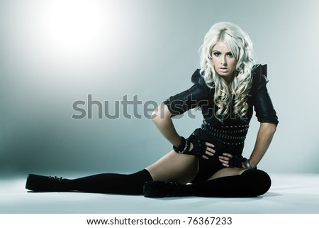 Young blonde in attractive high fashion black clothes with stockings - stock photo