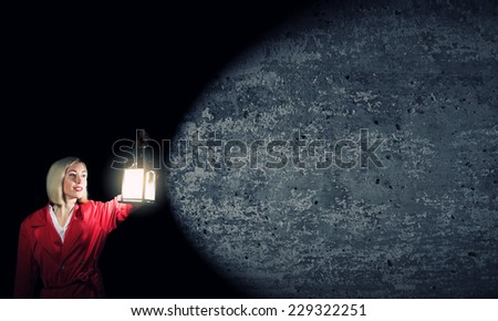 Young blonde in red cloak with lantern in darkness