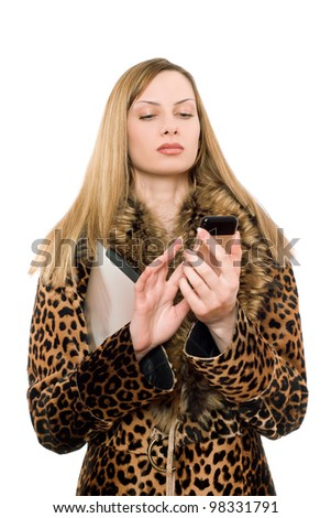 Young blonde in the fur coat calling - stock photo