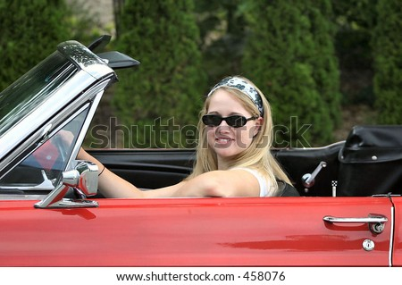 young blonde lady behind the steering wheel of a red antique convertible sports car - stock photo