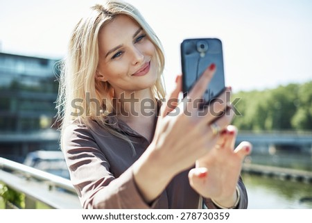 Young blonde lady with a smartphone - stock photo