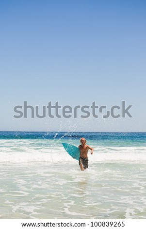 Young blonde man running in the water while returning to the beach - stock photo