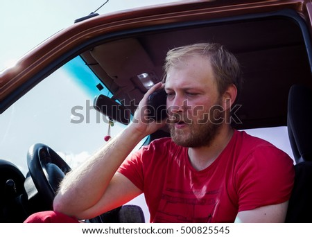 young blonde man speak telephone seating in his car, blonde man with blonde beard in red clothes speak with someone with telephone in right hand against car and blue sky