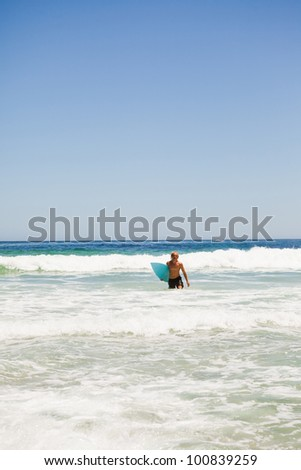 Young blonde man walking in the water while holding his blue surfboard - stock photo