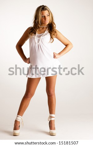 Young blonde model posing for the camera against a white wall