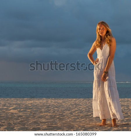 young blonde model posing on the white sands of Brazil on the background of the Atlantic Ocean
