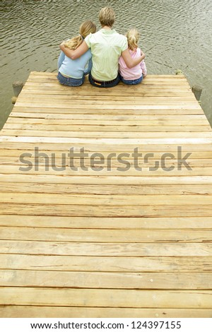 Young blonde mother and her two daughters sitting close together on the end of a wooden jetty alongside a lake. - stock photo