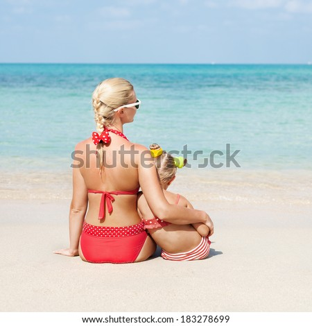 Young blonde mother hugging her little daughter sitting in the sand on the sea beach in summer. Outdoors - stock photo