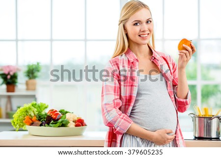 Young blonde pregnant woman cooking in kitchen. Woman holding apple and smiling. Concept for healthy lifestyle - stock photo