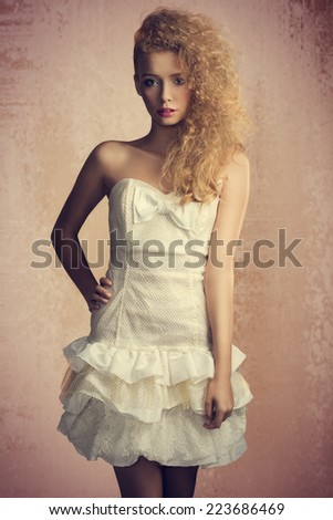 Young, blonde, pretty girl with curly hairstyle and romantic look. She is wearing white, gorgeous dress with a loop and colorful makeup. She is looking at camera.