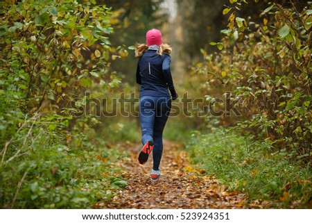 Young blonde runs among trees