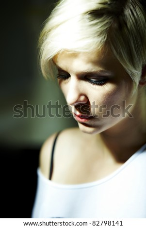 Young blonde sad woman looks at the ground - stock photo