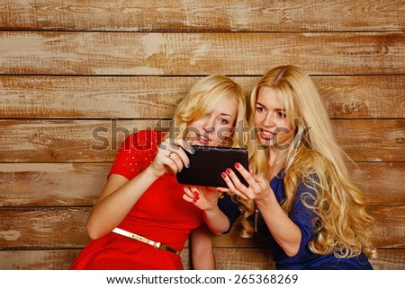 Young blonde sisters look carefully at the screen tablet computer, read the latest news of social networks on the Internet. The concept of youth and technology. - stock photo