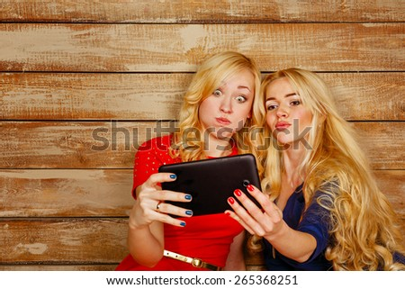 Young blonde sisters make fun group self, holding a tablet computer. Girl communicate in social networks. The concept of youth and technology. - stock photo