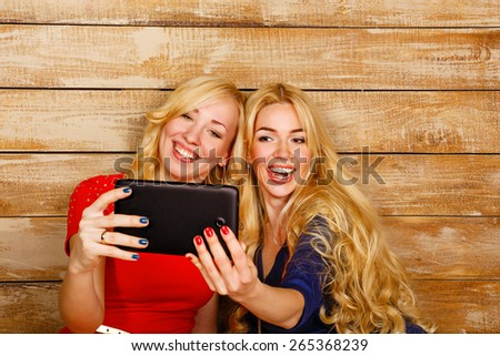 Young blonde sisters make fun group self, holding a tablet computer. Girls communicate by video conferencing on Internet. Girl having fun and positive emotions. The concept of youth and technology. - stock photo