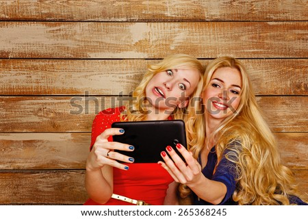 Young blonde sisters make fun group self, holding a tablet computer. Girls fool around communicating on the Internet. The concept of youth and technology. - stock photo