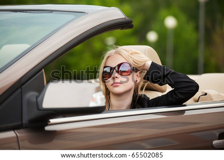 Young blonde sitting in a car. - stock photo