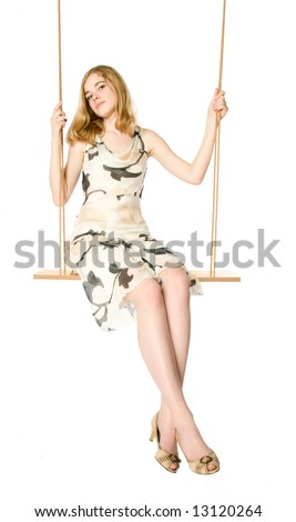 Young blonde sitting on a swing, white background - stock photo