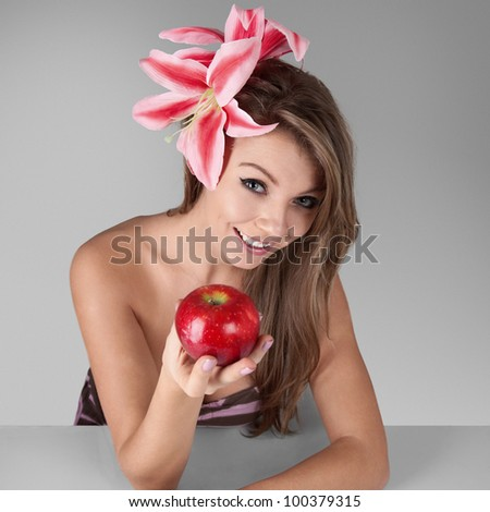 Young blonde smiling woman holding red fresh apple in hand