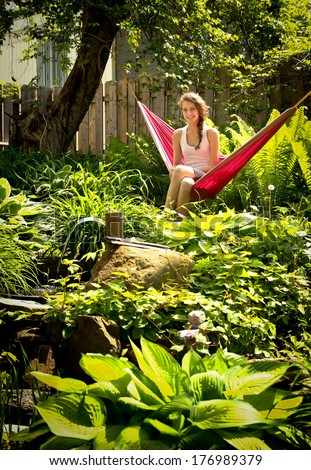 Young blonde teenager sit in a red hammock surround by green plants