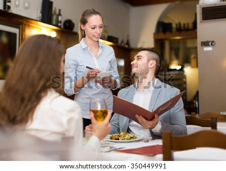 Young blonde waitress offering tasty dishes to smiling guests couple. Selective focus - stock photo