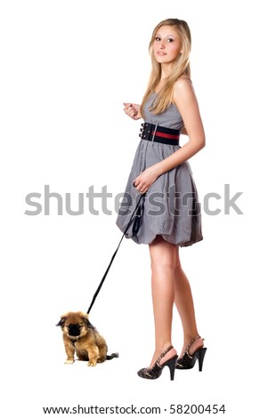 Young blonde walking over her pekingese puppy. Isolated on white - stock photo
