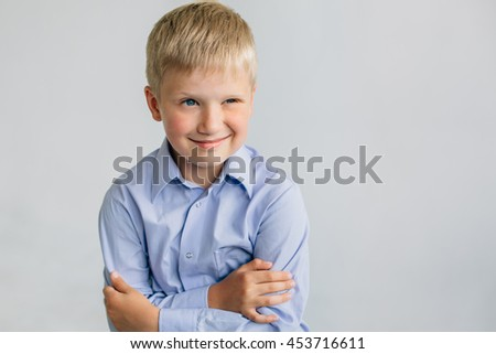 Young blonde winking boy in lilac shirt in front of  the white wall. Light background - stock photo