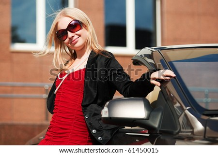 Young blonde with a convertible. - stock photo