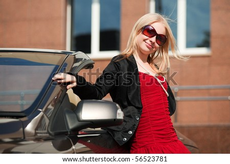 Young blonde with a her convertible. - stock photo