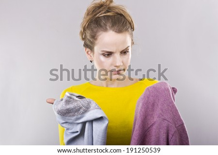 young blonde with clothes in hands - stock photo