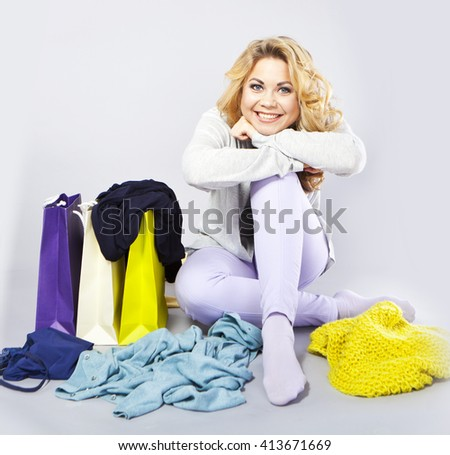 young blonde with clothes in hands.Hostess thinks how to save clothes. Means for care of clothes, washing powder, conditioner for clothes. Shopping