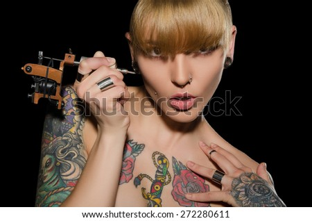 young blonde with tattoo machine and for them, dark background - stock photo