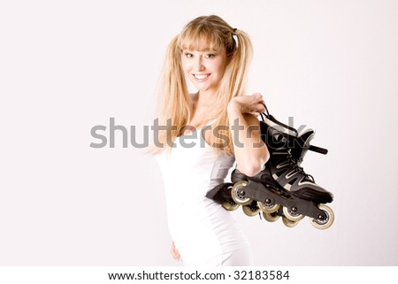 young blonde with white sportswear and plaits with roller-skates on the shoulder - stock photo
