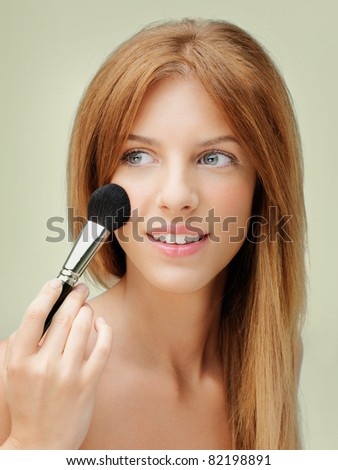 young blonde woman applying blusher with brush - stock photo