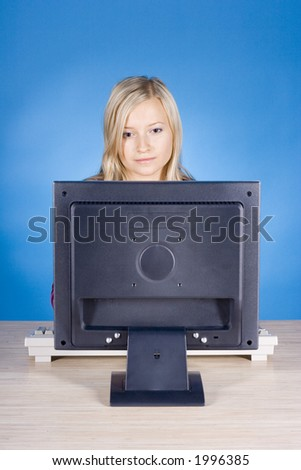 young blonde woman at the computer (blue background) - stock photo